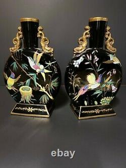A pair of opaque, flat and round, gilded and painted black opaline glass vases